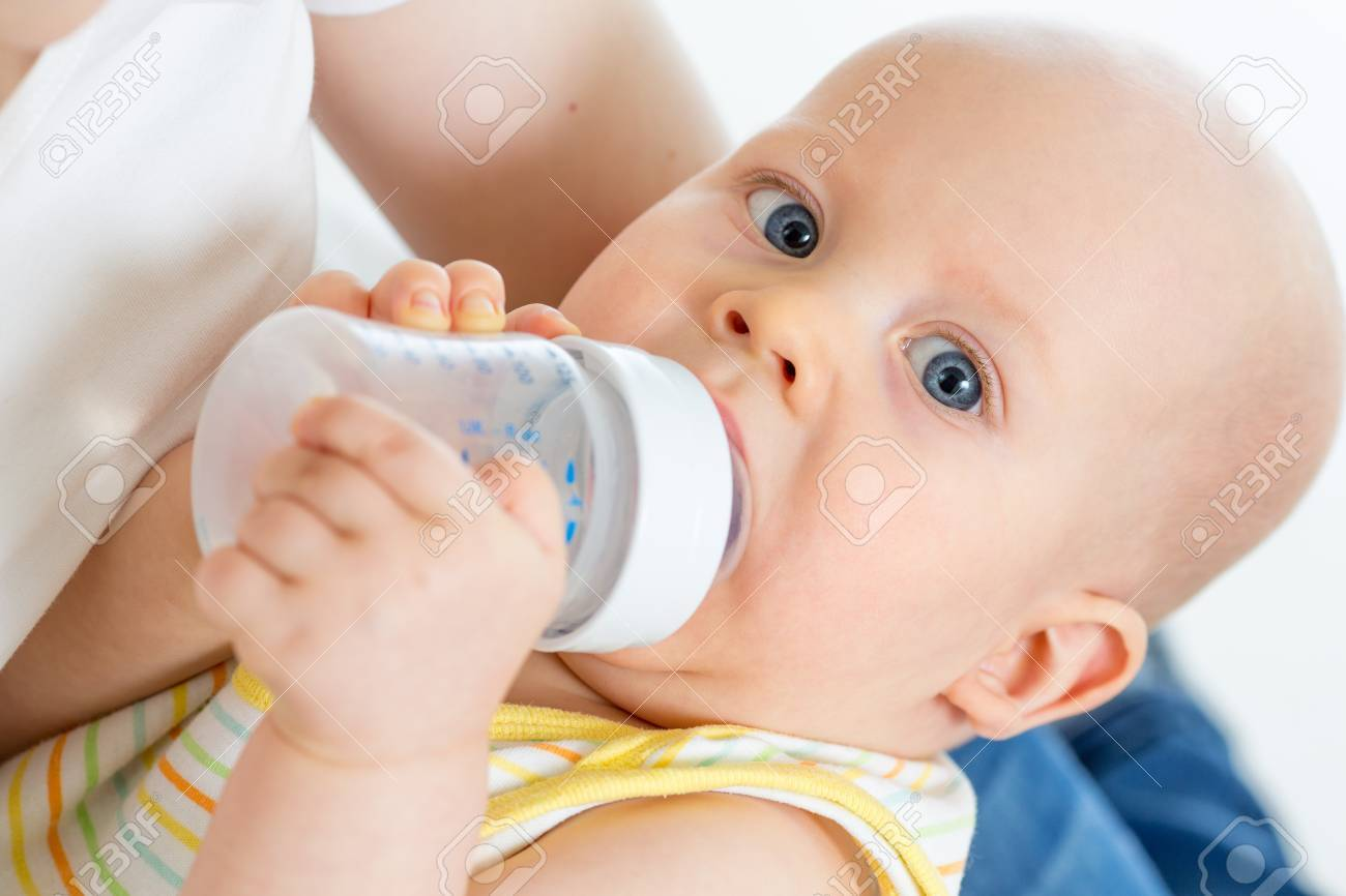 Pretty baby boy drinking milk or water from bottle Stock Photo - 17499553