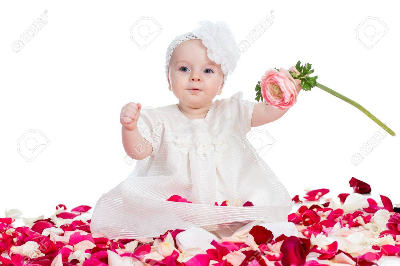 cute baby girl with flower sitting among rose petals stock photo