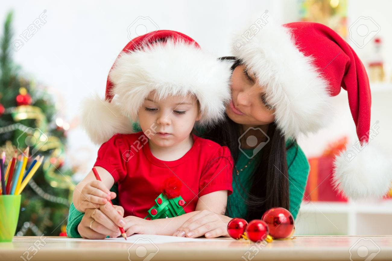 child girl and mom writing christmas letter to santa claus stock