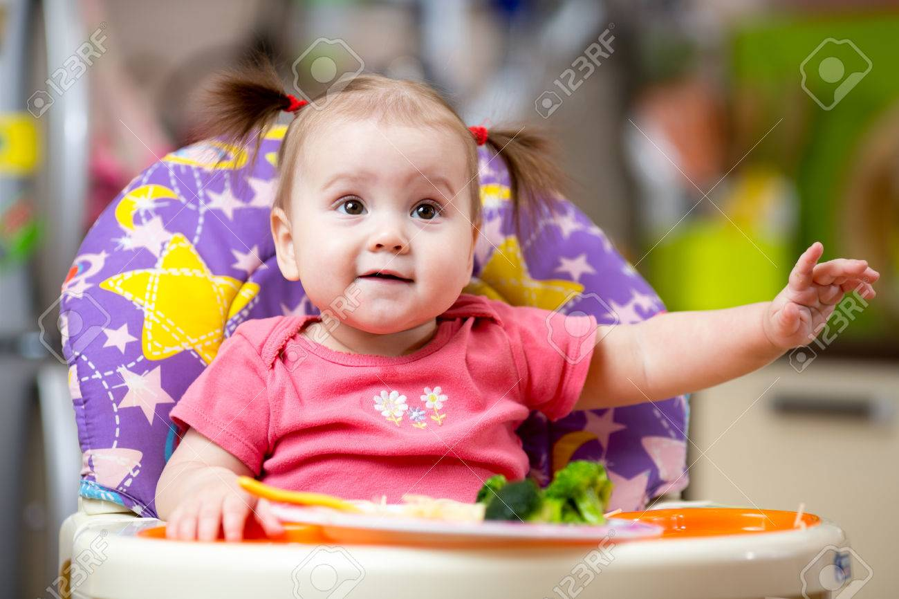 cute baby girl eating healthy food on kitchen stock photo, picture