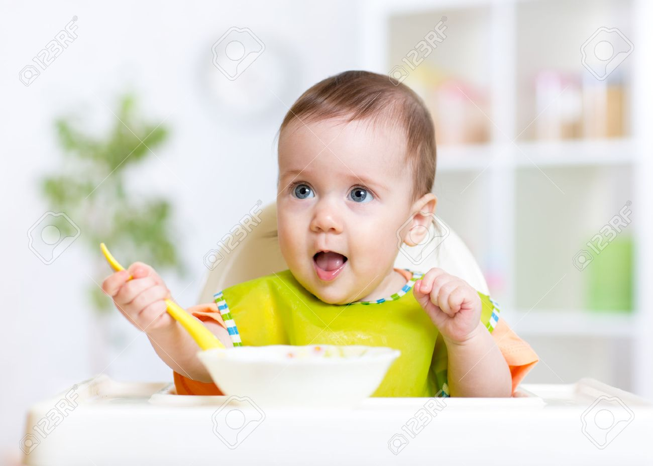happy cute baby kid eating food itself with spoon stock photo