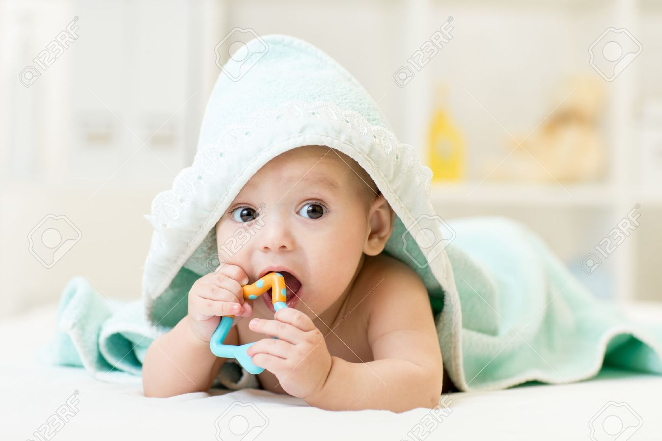 baby with teether in mouth under bathing towel at nursery Stock Photo - 42593610