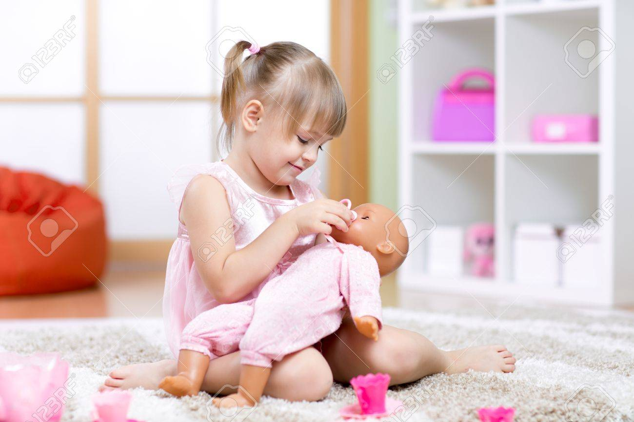 bef4fb52b948e child girl playing with her baby-doll in day care center Stock Photo -  44258198