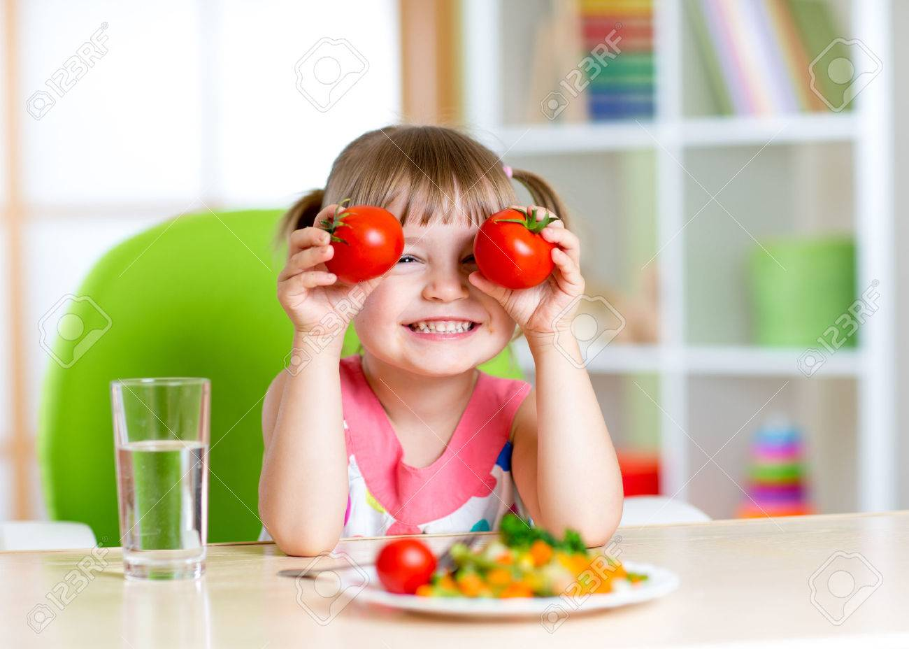 Child with tomatoes. Happy little girl with vegetables at home. - 44393942