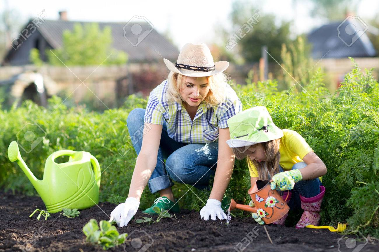 kid watering plant woman and child girl mother and daughter gardening together planting