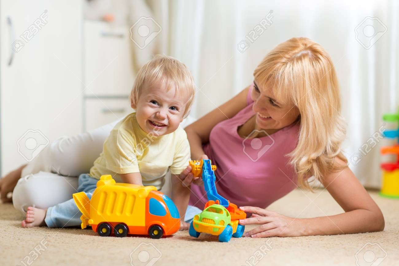 Happy Mother And Child Boy Play With Car Toys Together At Home Stock