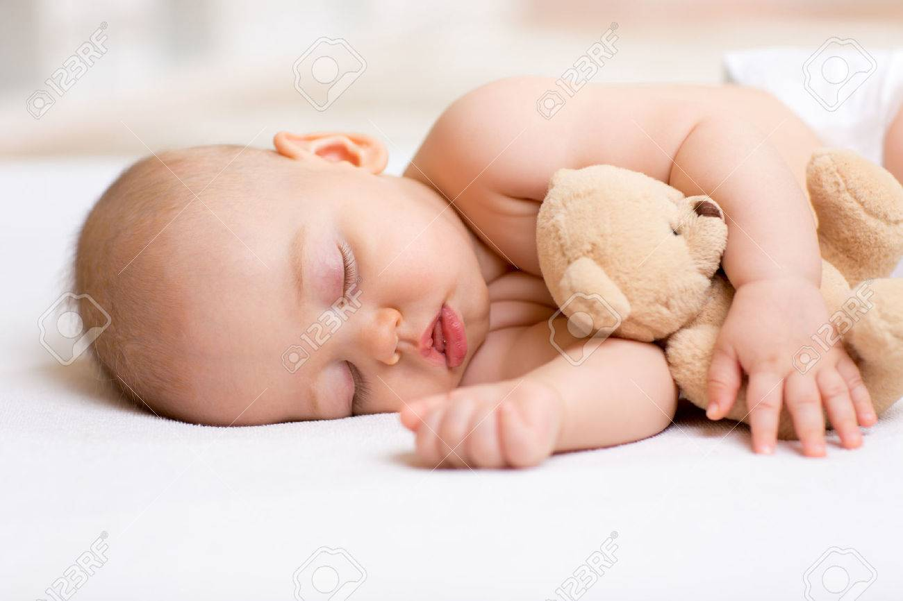Carefree sleep baby boy with soft toy on bed Stock Photo - 48204923