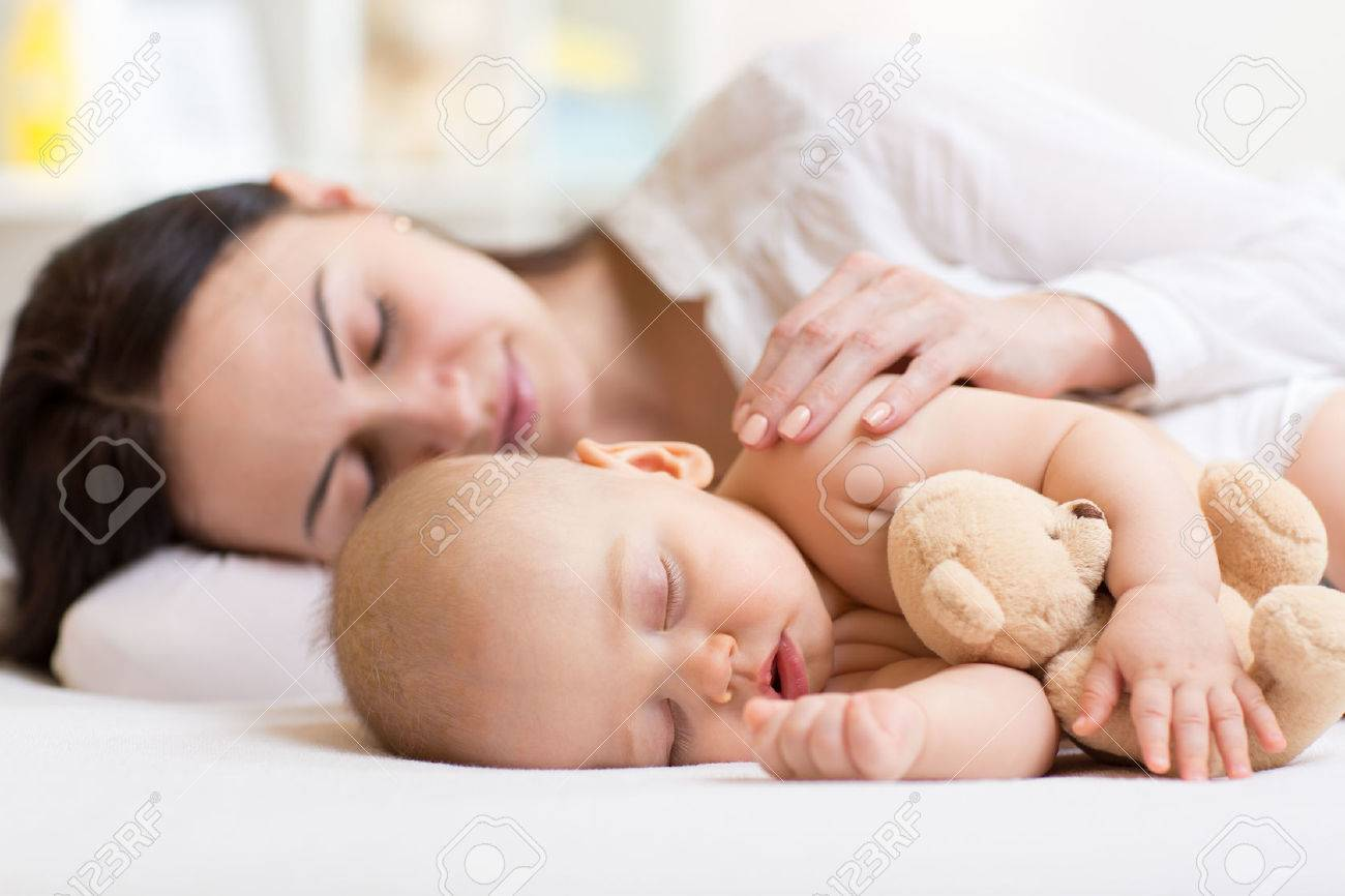 beautiful woman and her son little baby sleeping together in a bedroom Stock Photo - 48931126