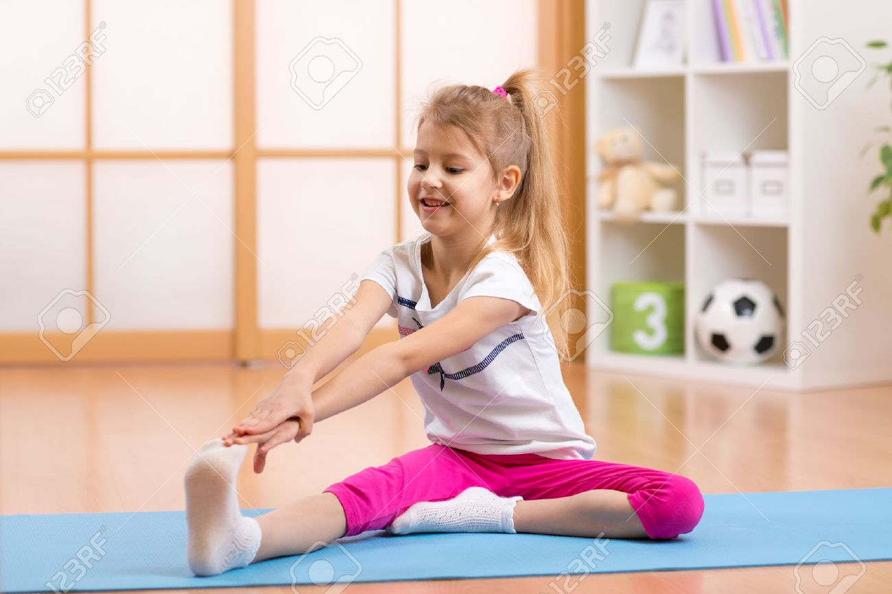 Sportive kid girl doing gymnastic at home Stock Photo - 48954103