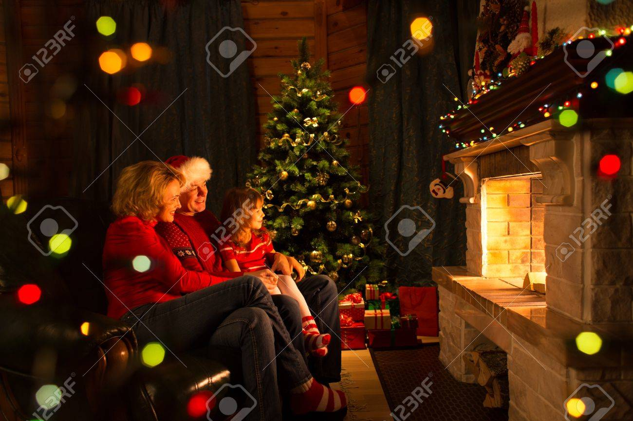 Happy family - mother, father and their daughter by a fireplace on Christmas Stock Photo - 49005133