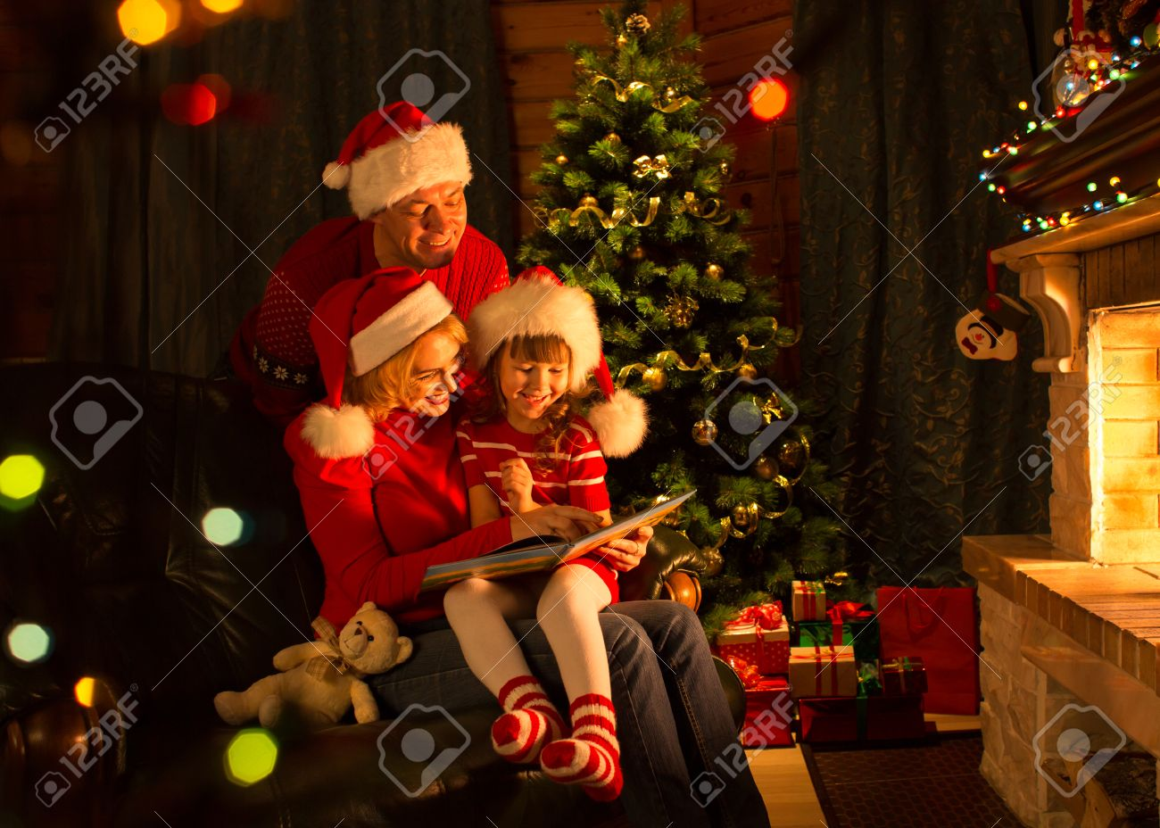 happy family read book by christmas tree in cozy living room