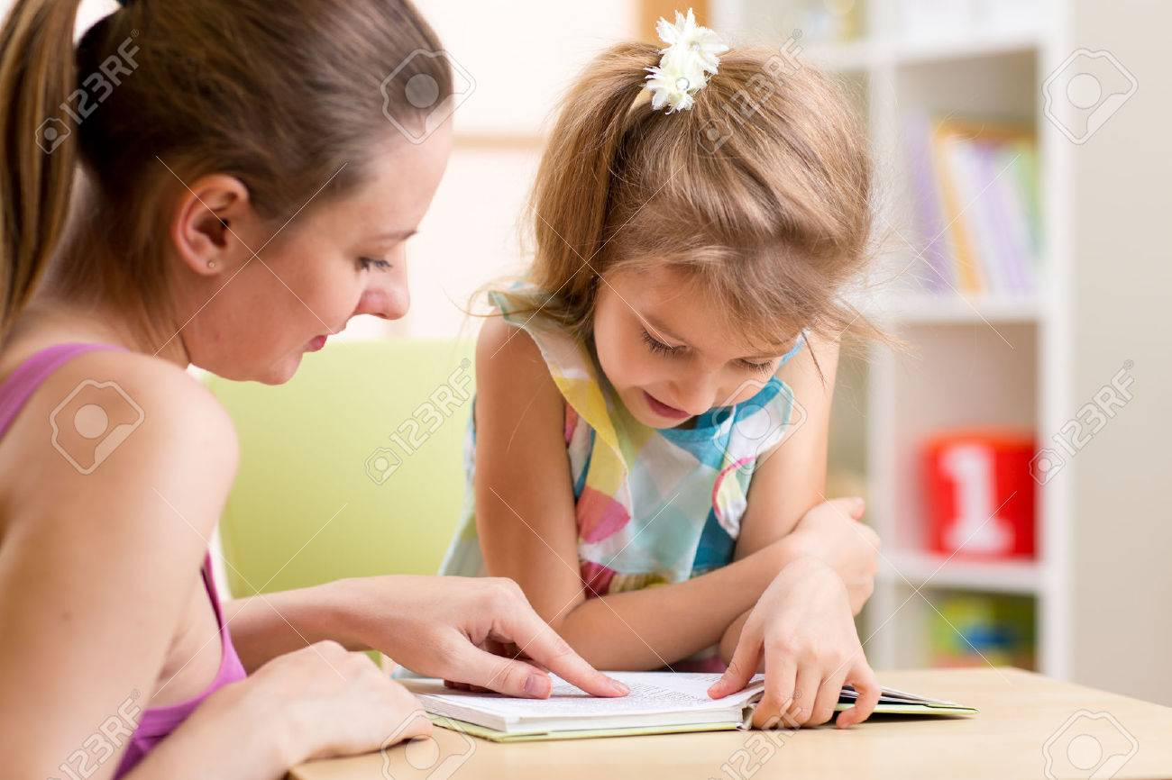 Mother teaching her child daughter to read Stock Photo - 49361021