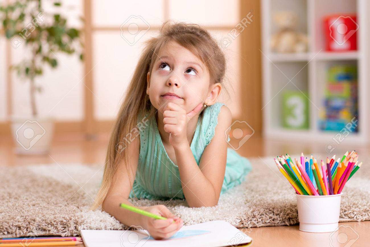 dreamy kid girl draws with color pencils lying on floor at home Stock Photo - 49900047