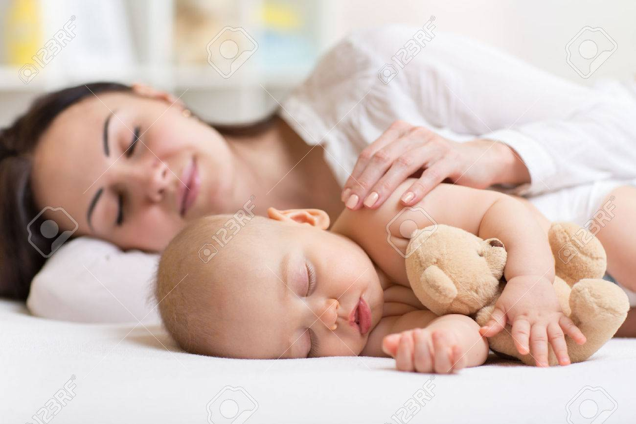 mother and her son baby sleeping together in a bedroom Stock Photo - 49900054