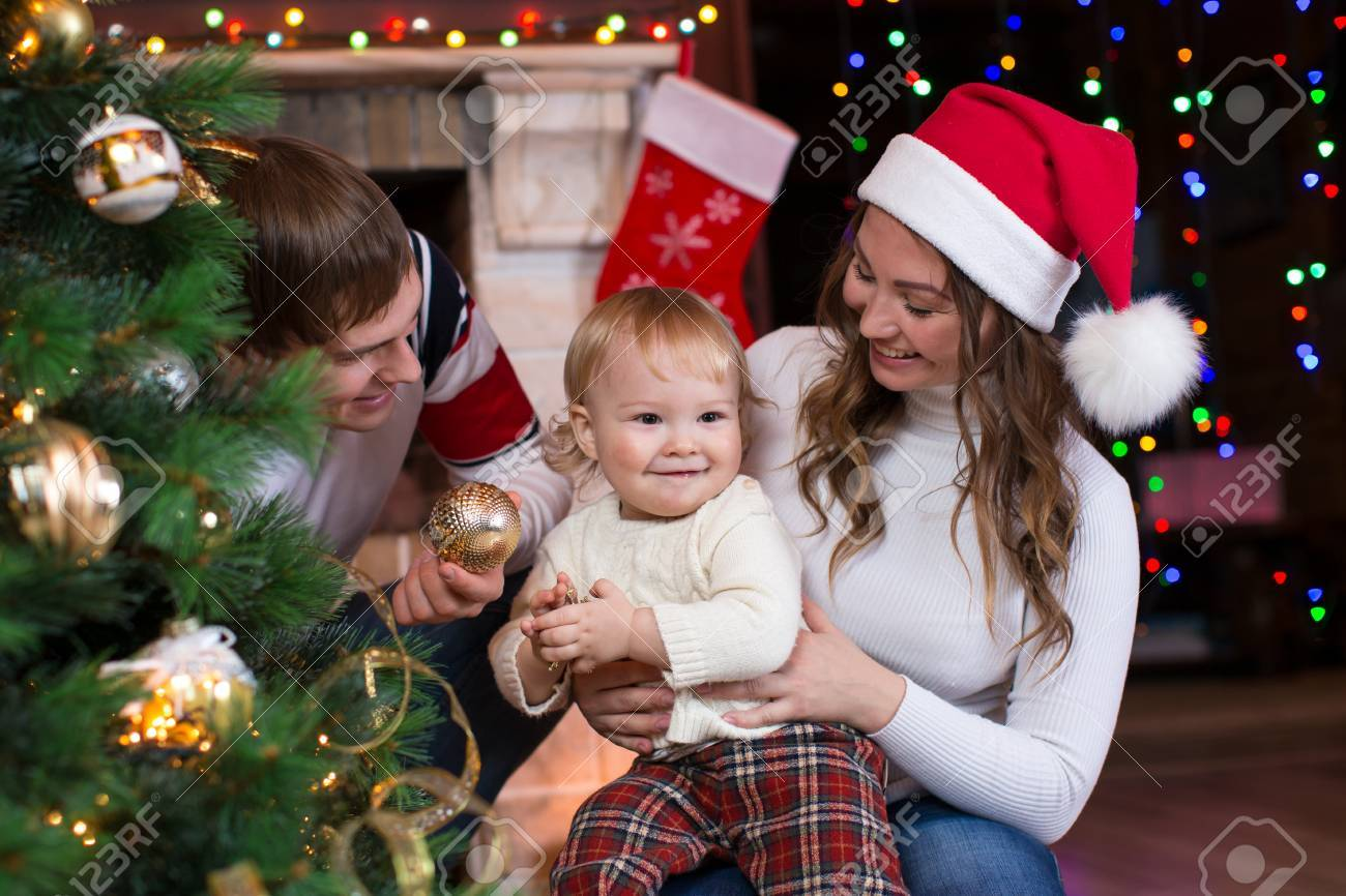Happy Family With Child Son Decorating Christmas Tree In Front
