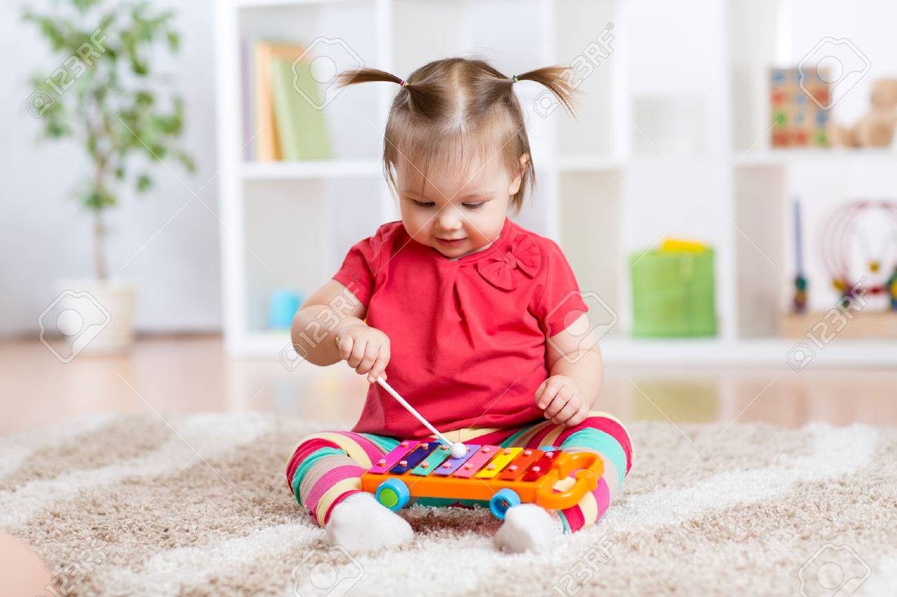 Child little girl plays a musical instrument xylophone sitting on the floor in the nursery Stock Photo - 51791343