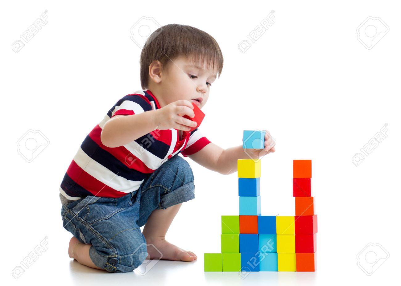 kid enfant garçon jouant avec des cubes de couleur jouets sur le plancher isolé Banque d'images - 52013162