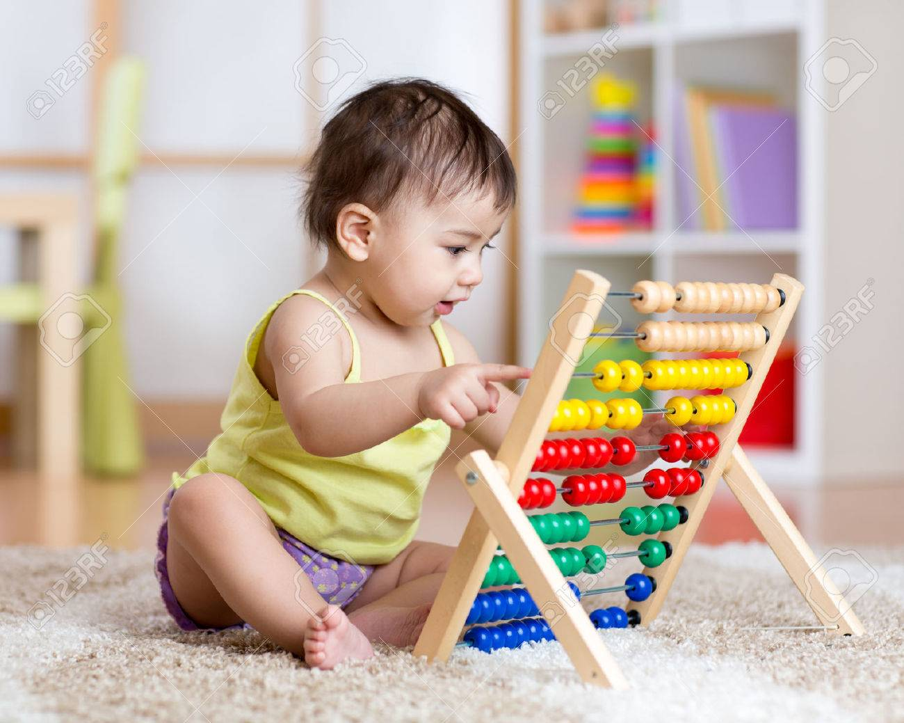 Cute baby boy playing with counter toy Stock Photo - 52545411