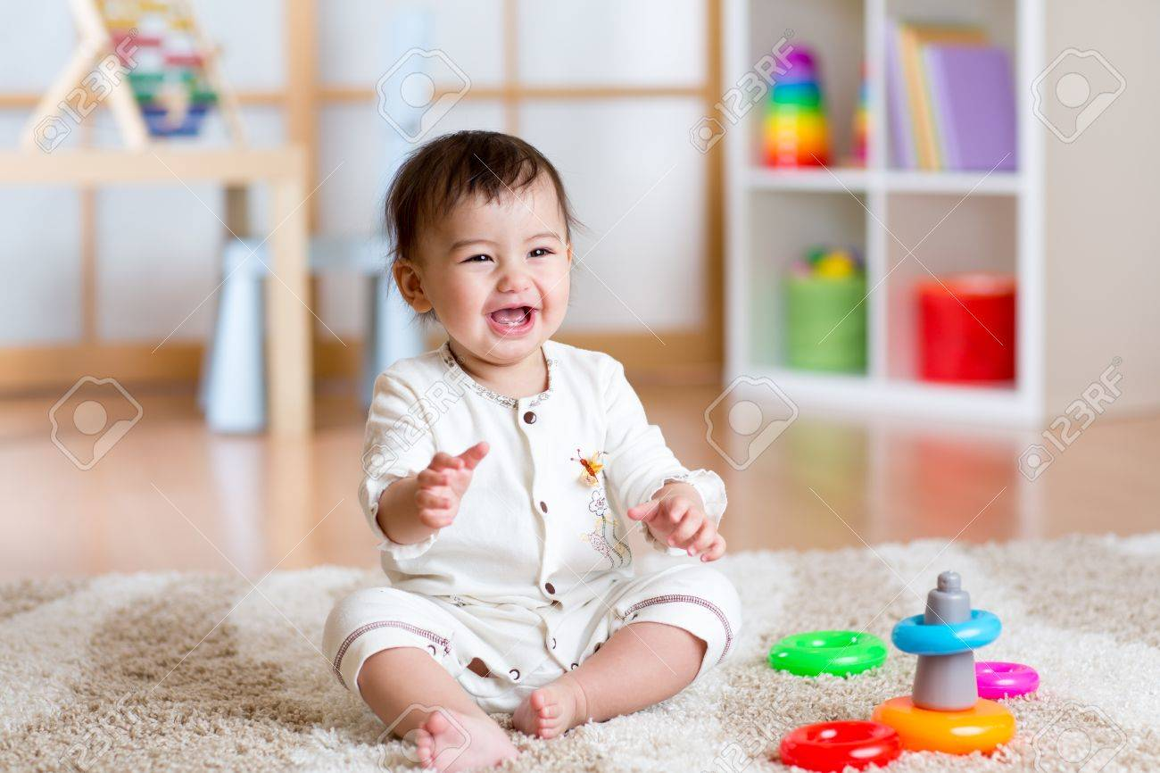 cute cheerful baby playing with colorful toy pyramid at home Stock Photo - 52541716
