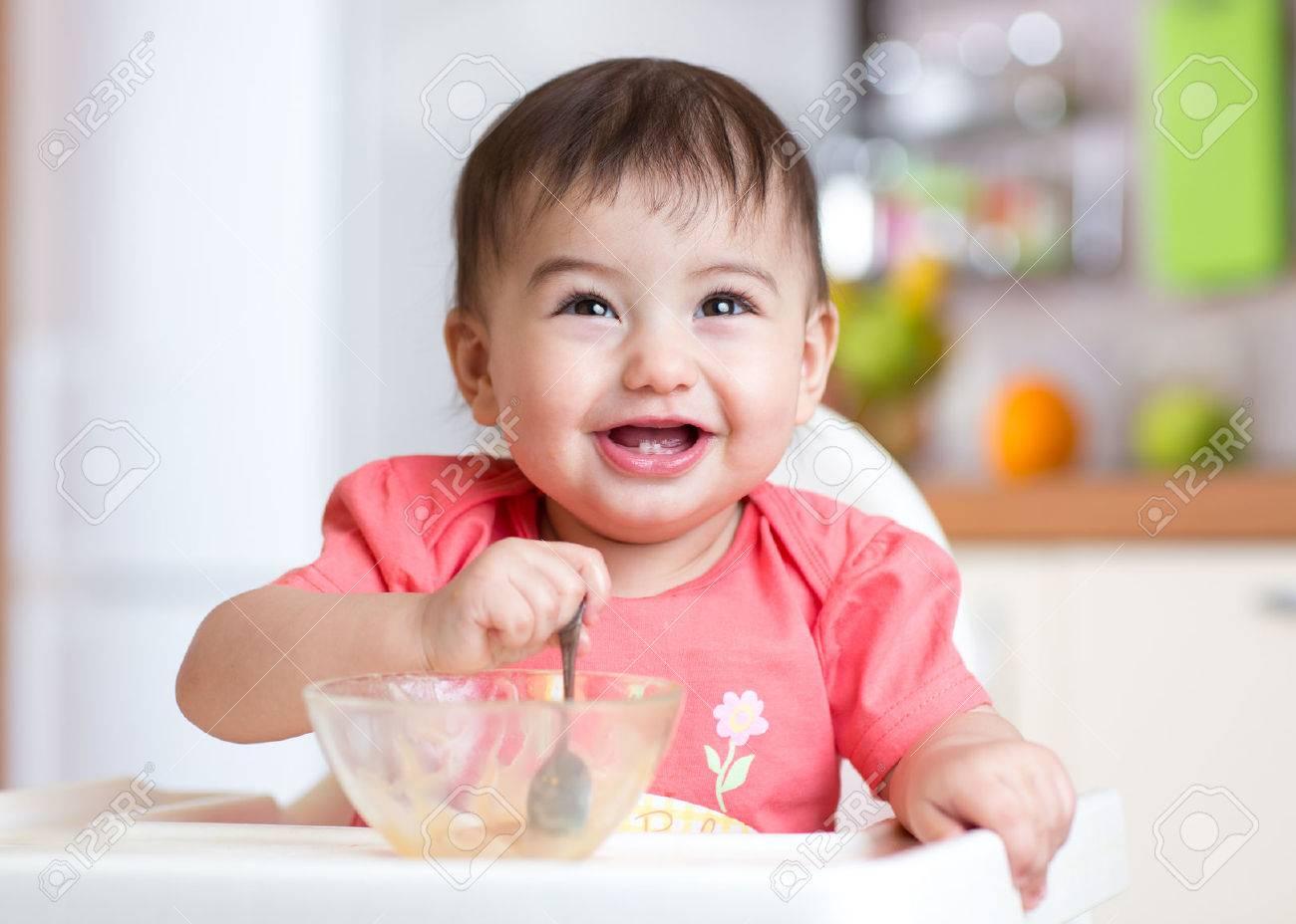 gai heureux aliments pour bébé enfant de manger lui-même avec une cuillère Banque d'images - 54306996