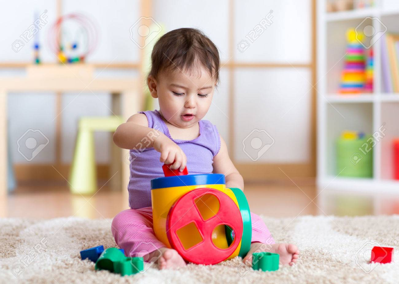 Cute toddler girl playing indoors with sorter toy sitting on soft carpet Stock Photo - 54307076