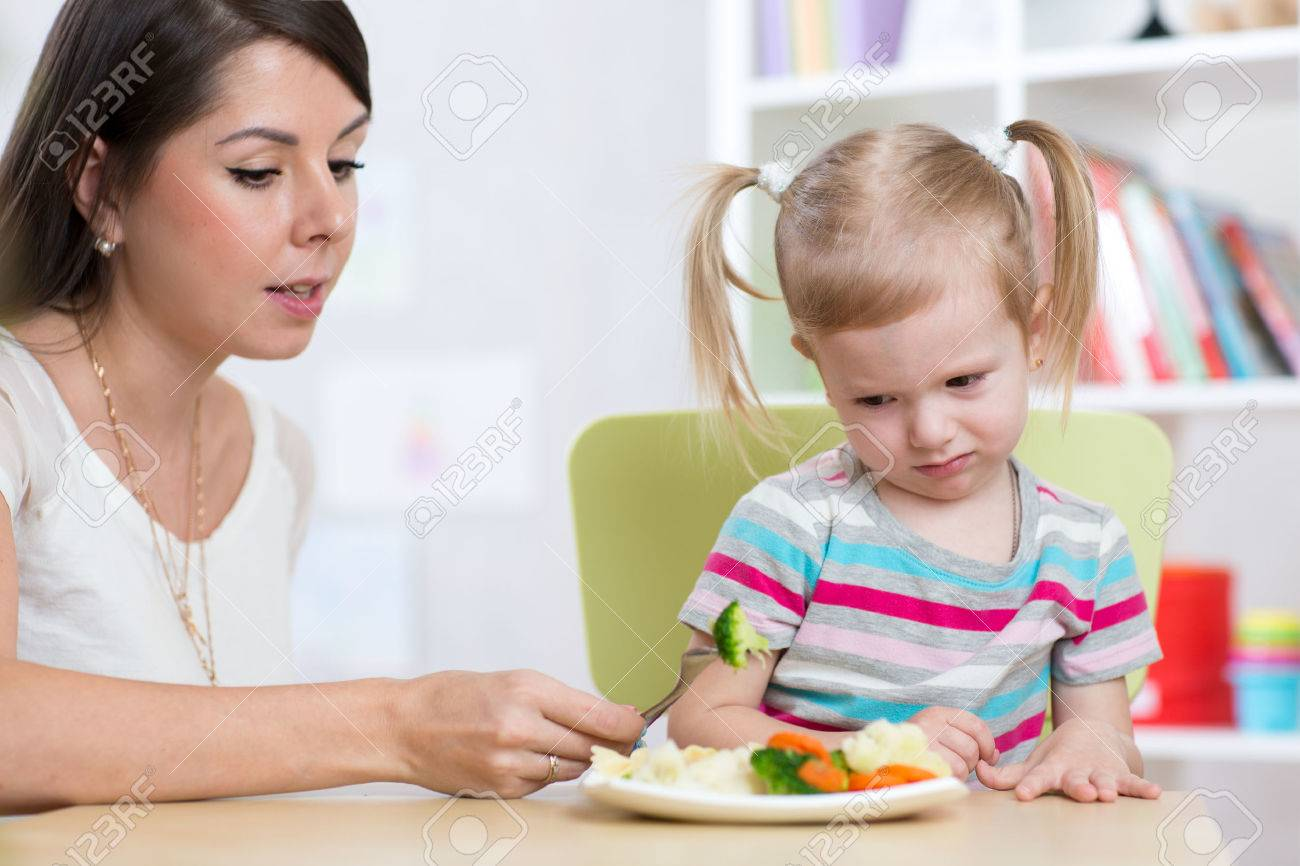 Child girl looks with disgust at healthy vegetables. Mom convinces daughter to eat food. Stock Photo - 54307054