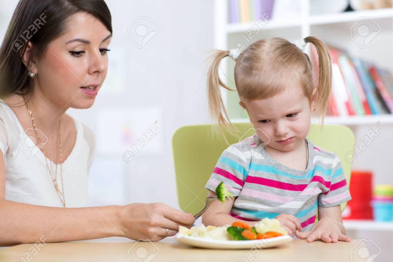 fille de l'enfant regarde avec dégoût des légumes sains. Maman convainc fille à manger de la nourriture. Banque d'images - 54307054