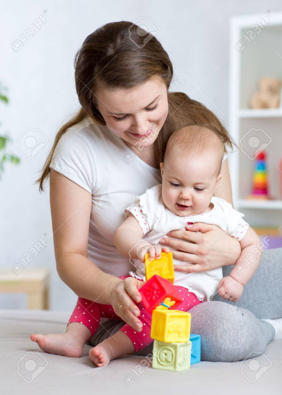 Mother and baby girl playing with educational toys in living