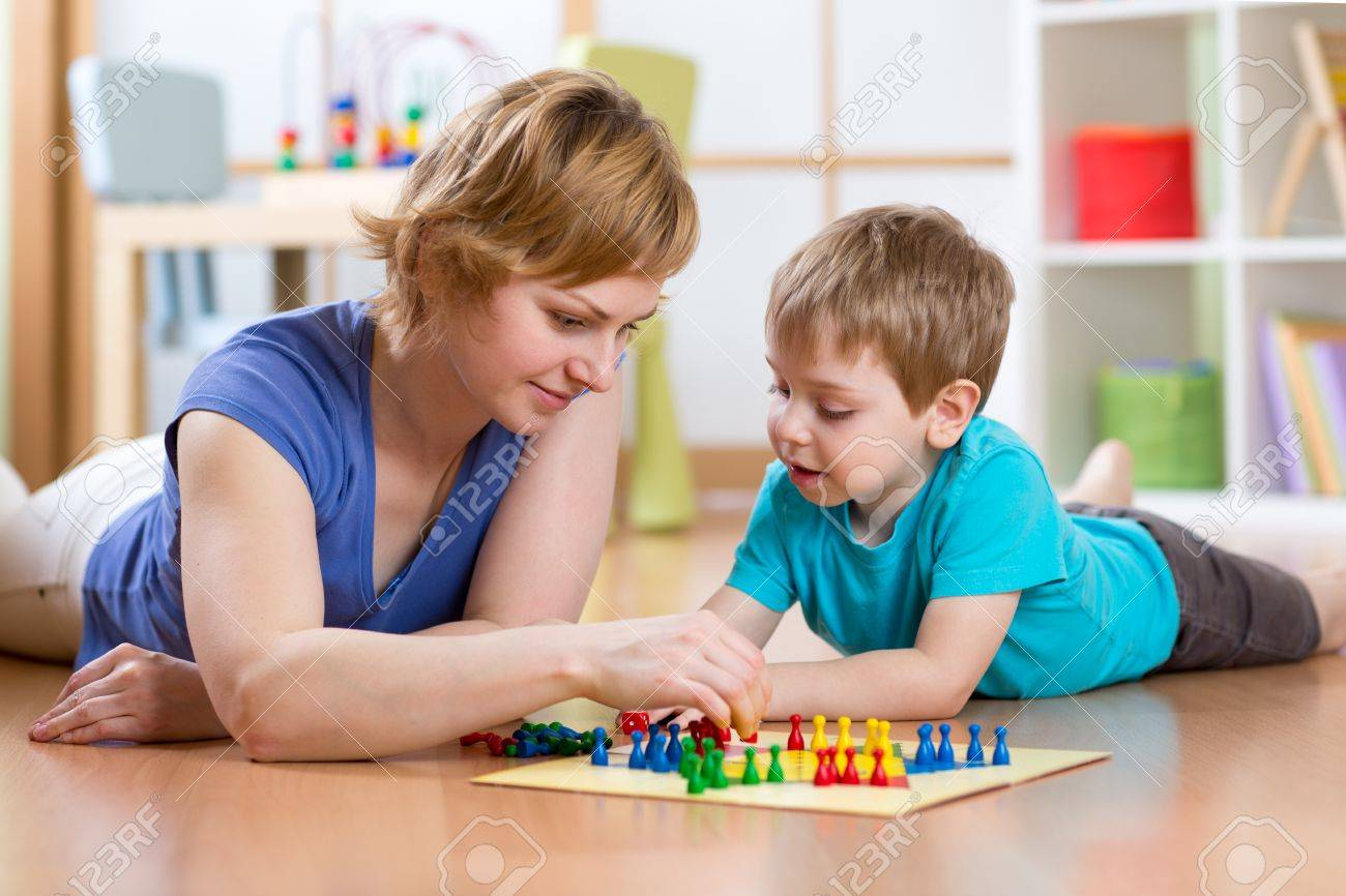Family mother and son kid playing board game ludo at home on the floor Banque d'images - 53471231