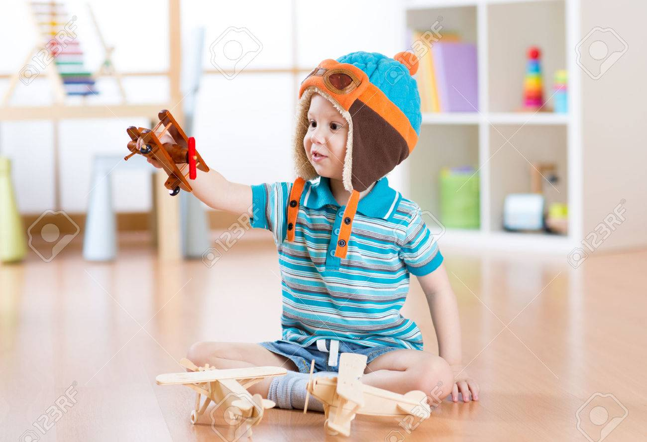 happy child toddler plays with toy airplane and dreaming of becoming a pilot Stock Photo - 53471275