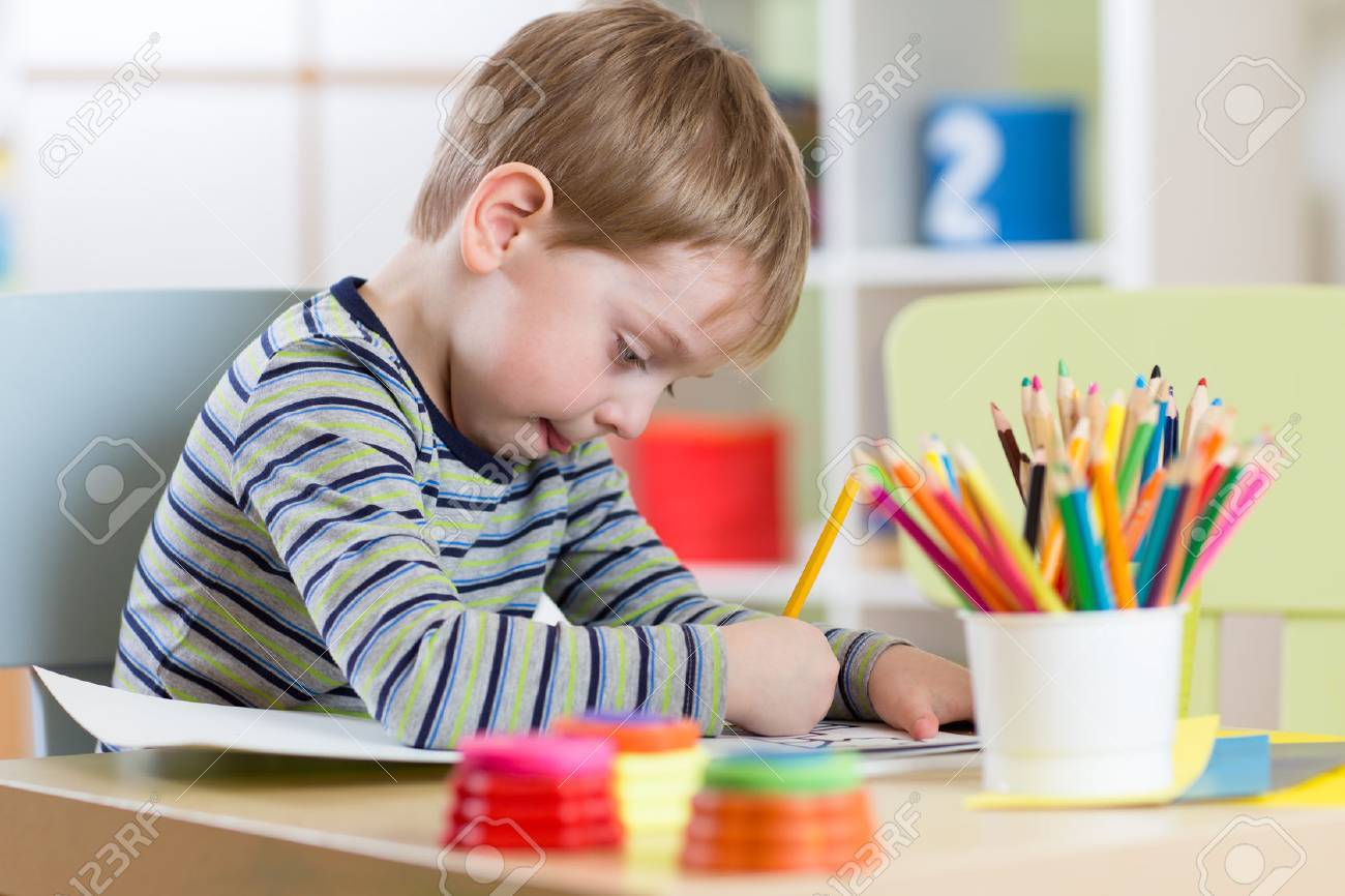 Preschool child boy use pencils and paints for homework received from kindergarten Stock Photo - 53471276