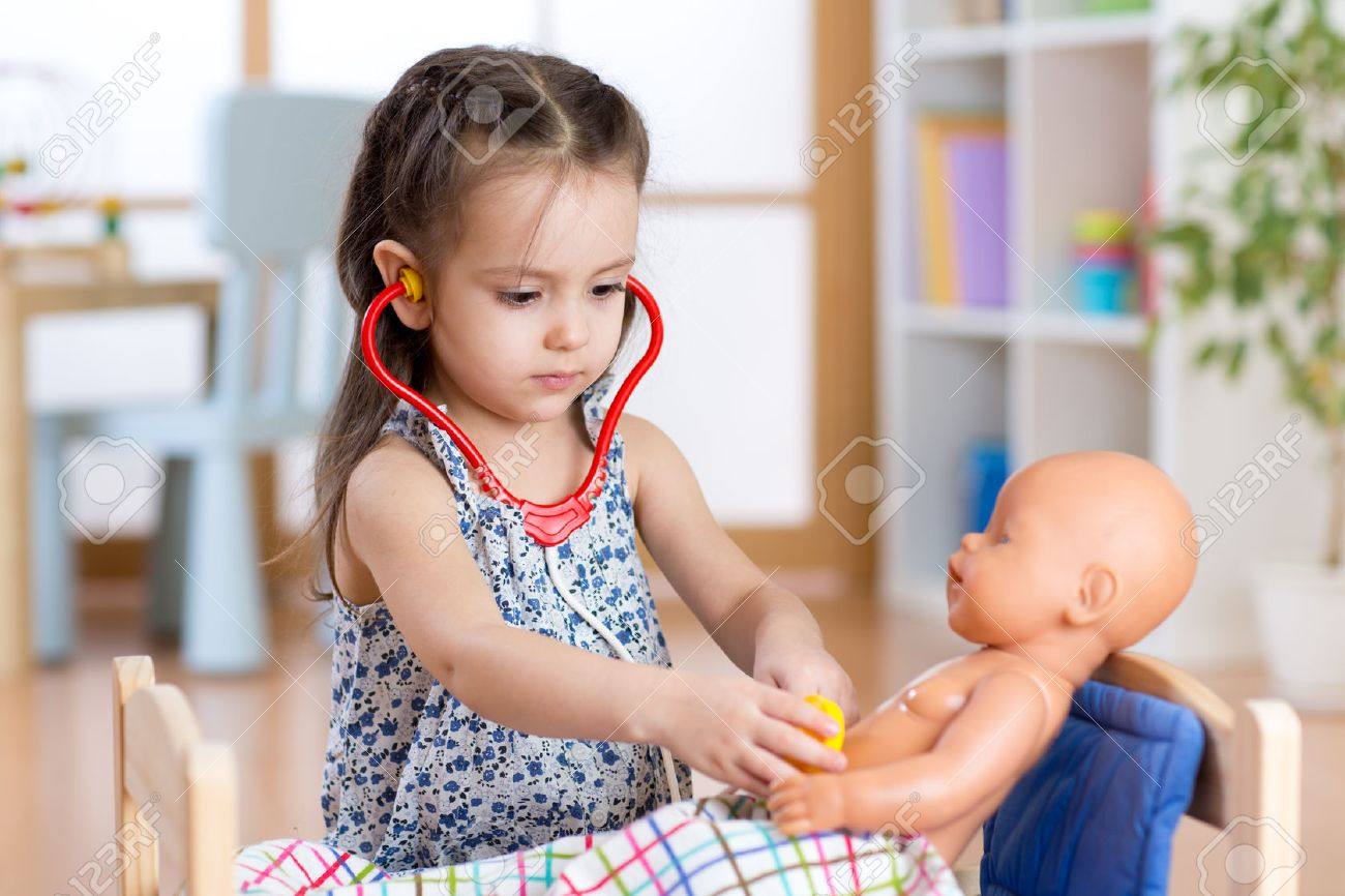 enfant fille jouer au docteur avec la poupée à la maison Banque d'images - 53471284