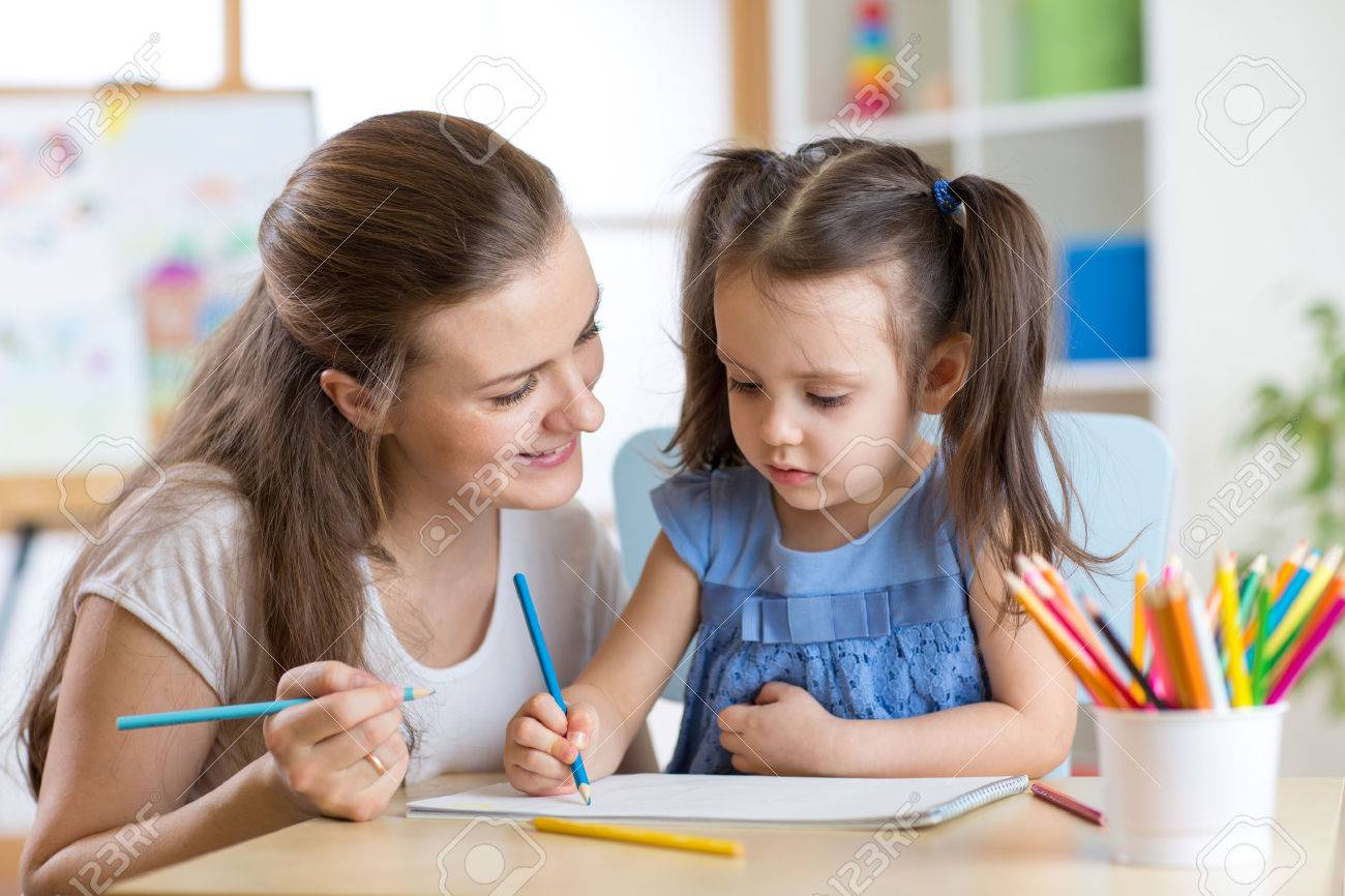 Young mother looking how her child daughter drawing a picture Stock Photo - 53471300