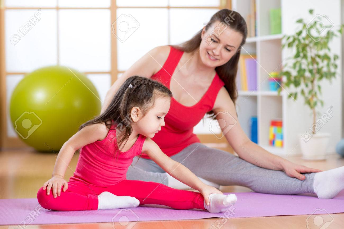 Mother and child daughter doing yoga exercises on mat at home Stock Photo - 53471305