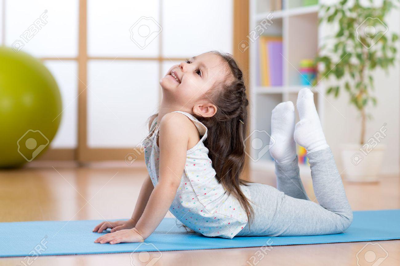 Kind Mädchen, Das Gymnastik Auf Der Matte Zu Hause Zu Tun ...