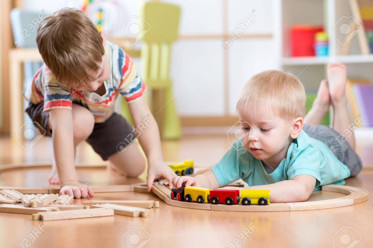 cute children playing with wooden train. toddler kids playing
