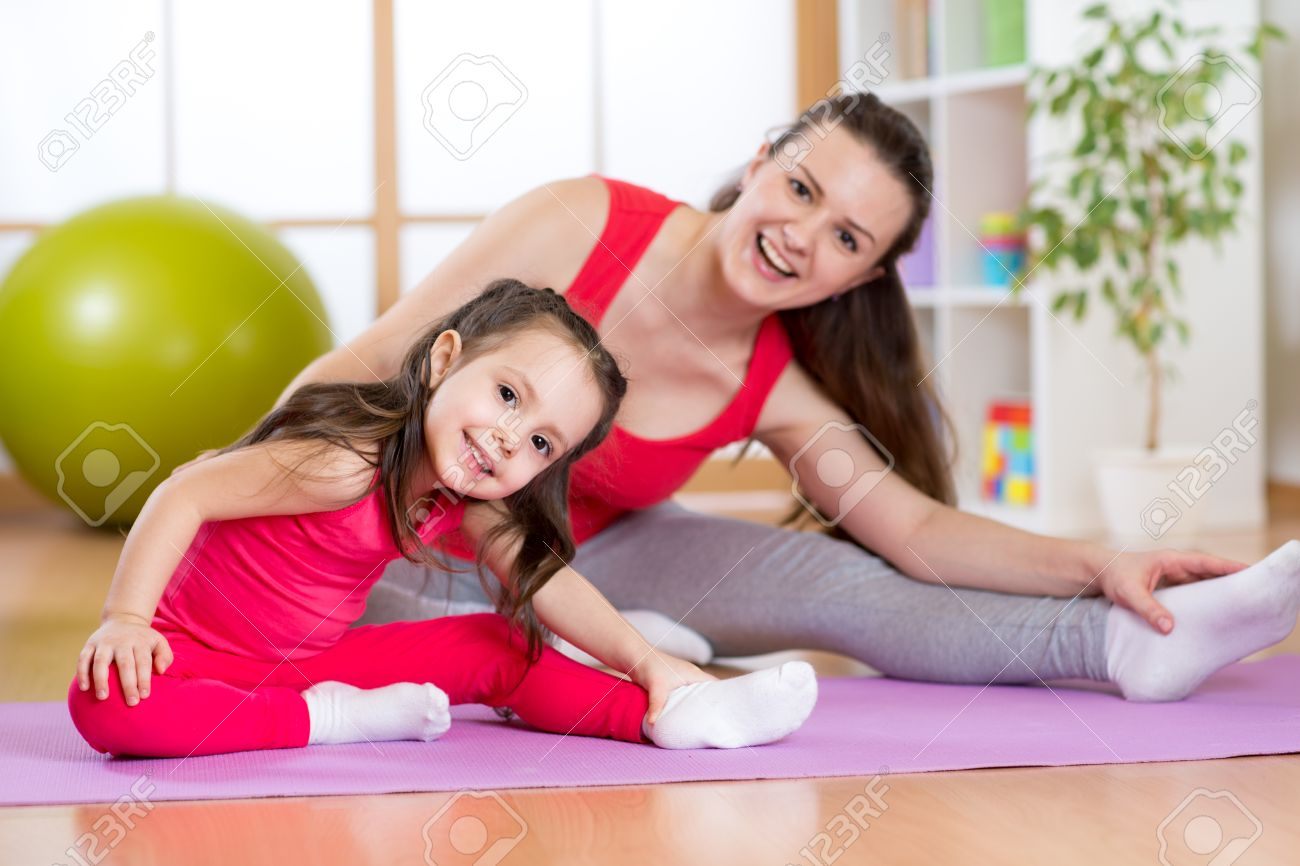 Portrait of kid girl and her mother doing gym exercise at home Stock Photo - 53851902