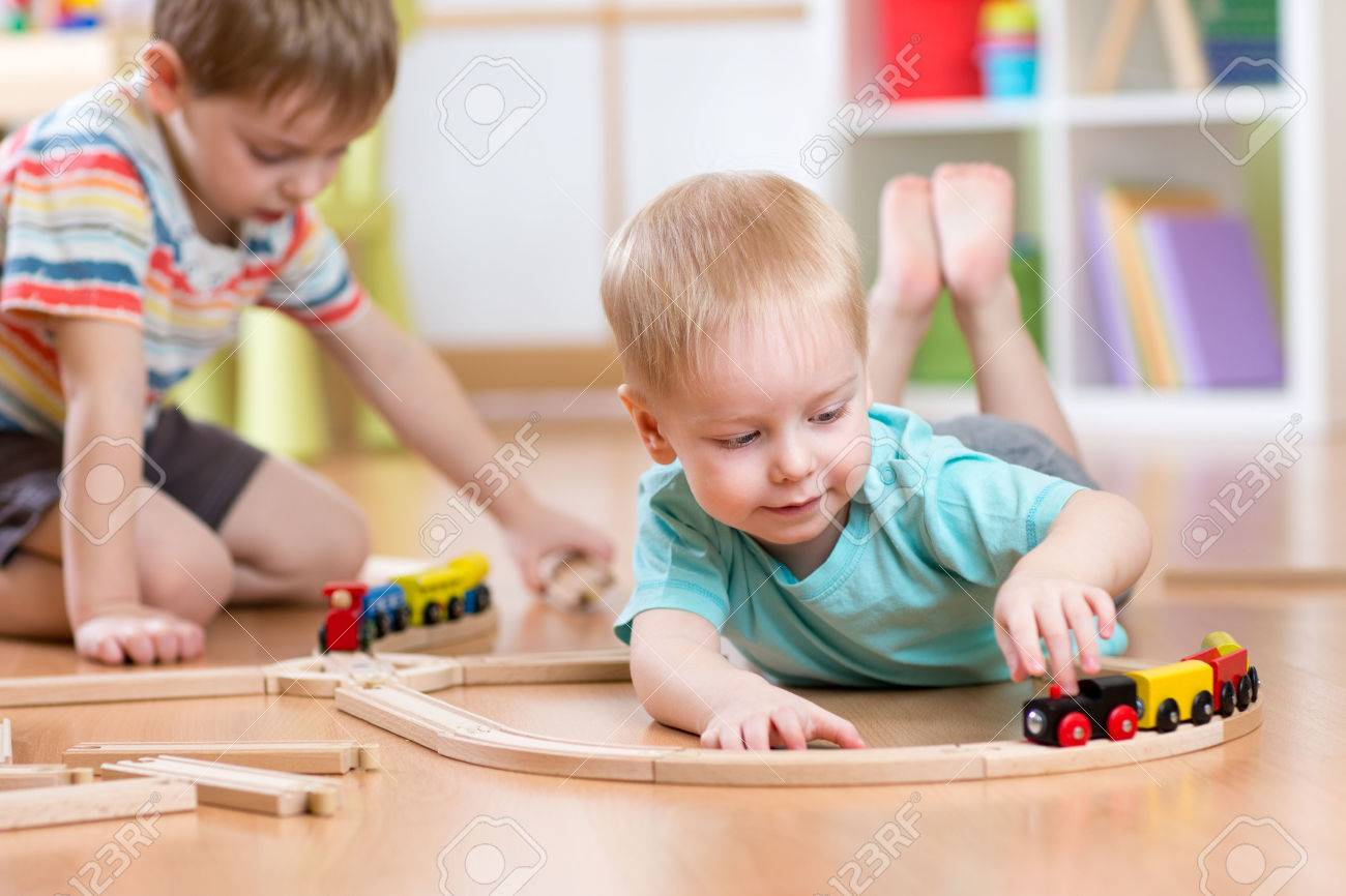 Children boys playing with wooden train set Stock Photo - 53851907