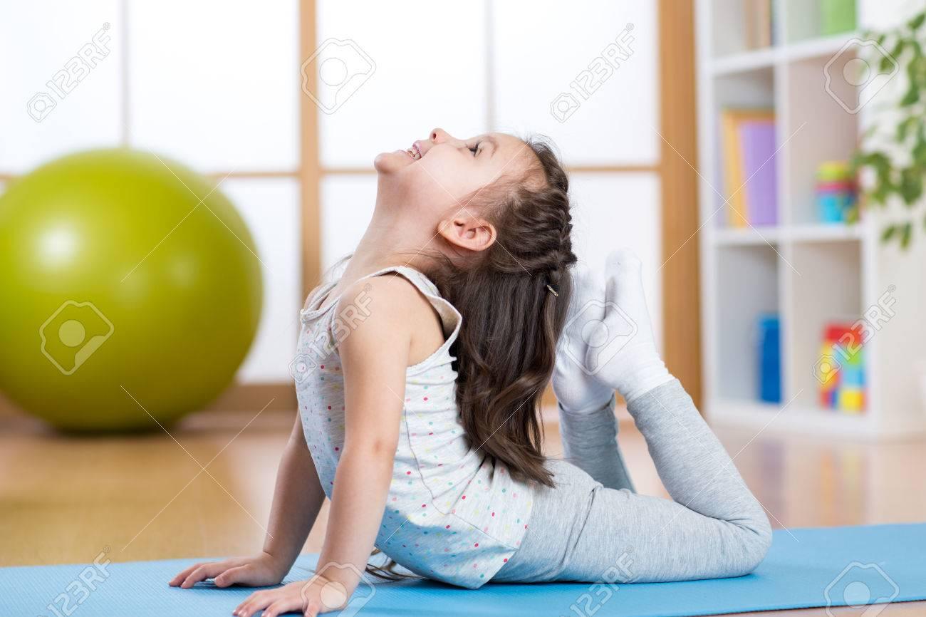 fille enfants faire de la gymnastique sur le tapis à la maison Banque d'images - 53851920