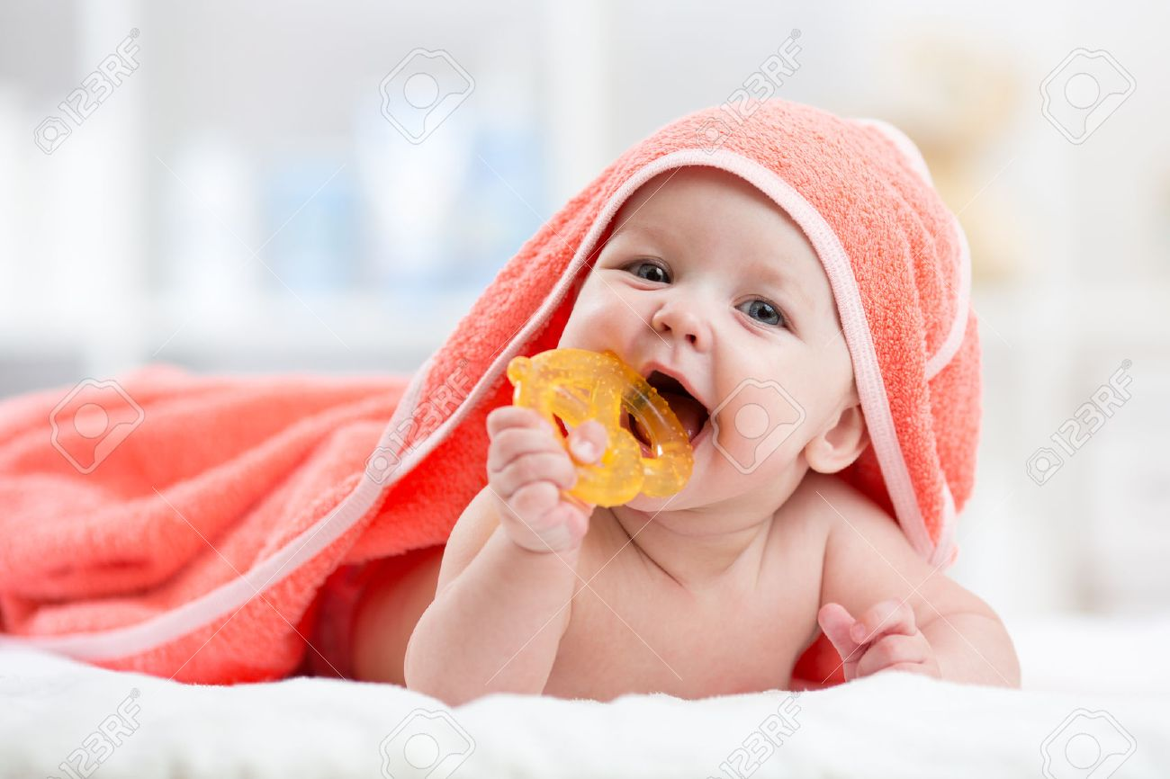 Cute baby with teether in mouth under a hooded towel after bath Stock Photo - 53851948