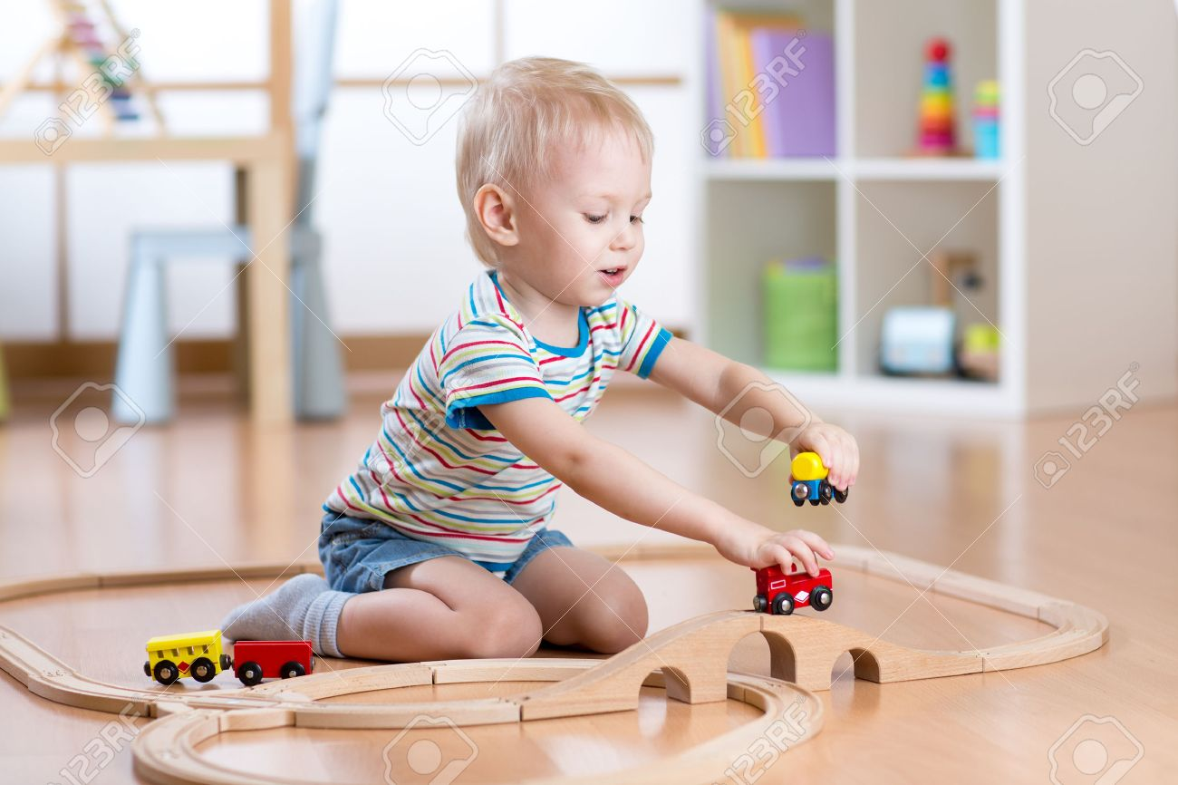 child boy playing with railway toys indoors at home - 53851951