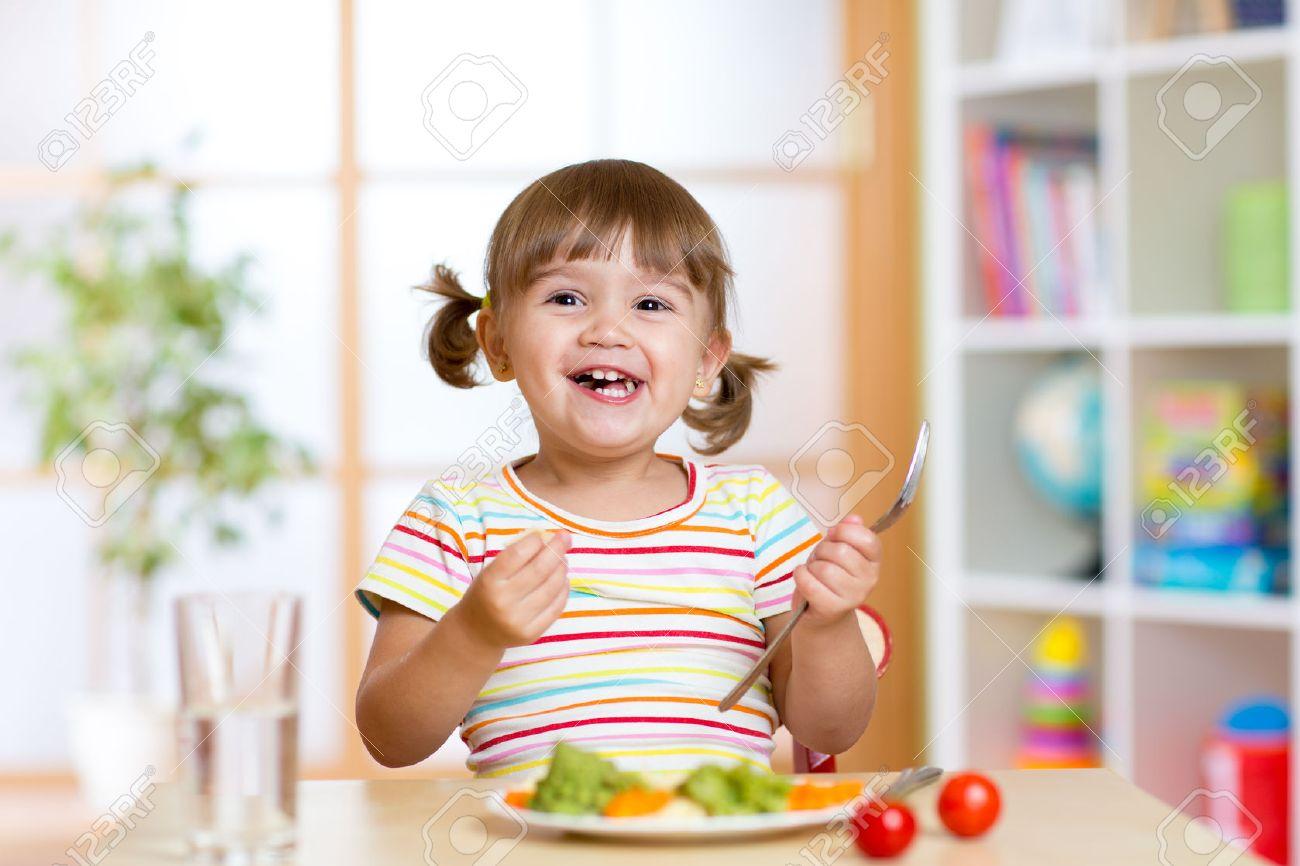Happy kid girl eating vegetables. Healthy nutrition for children Stock Photo - 54270212