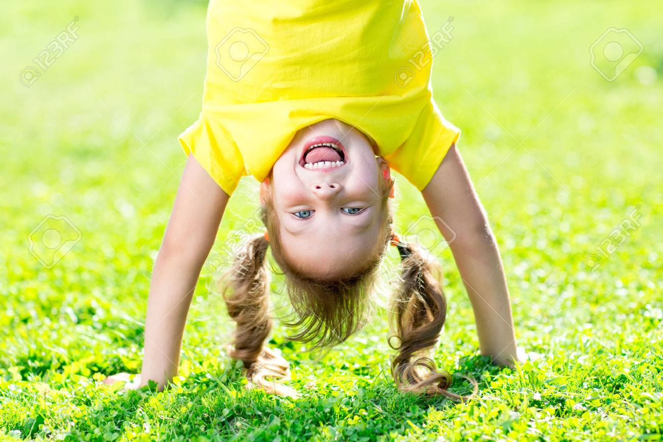 Portraits of happy kid playing upside down outdoors in summertime standing on hands Banque d'images - 54270324