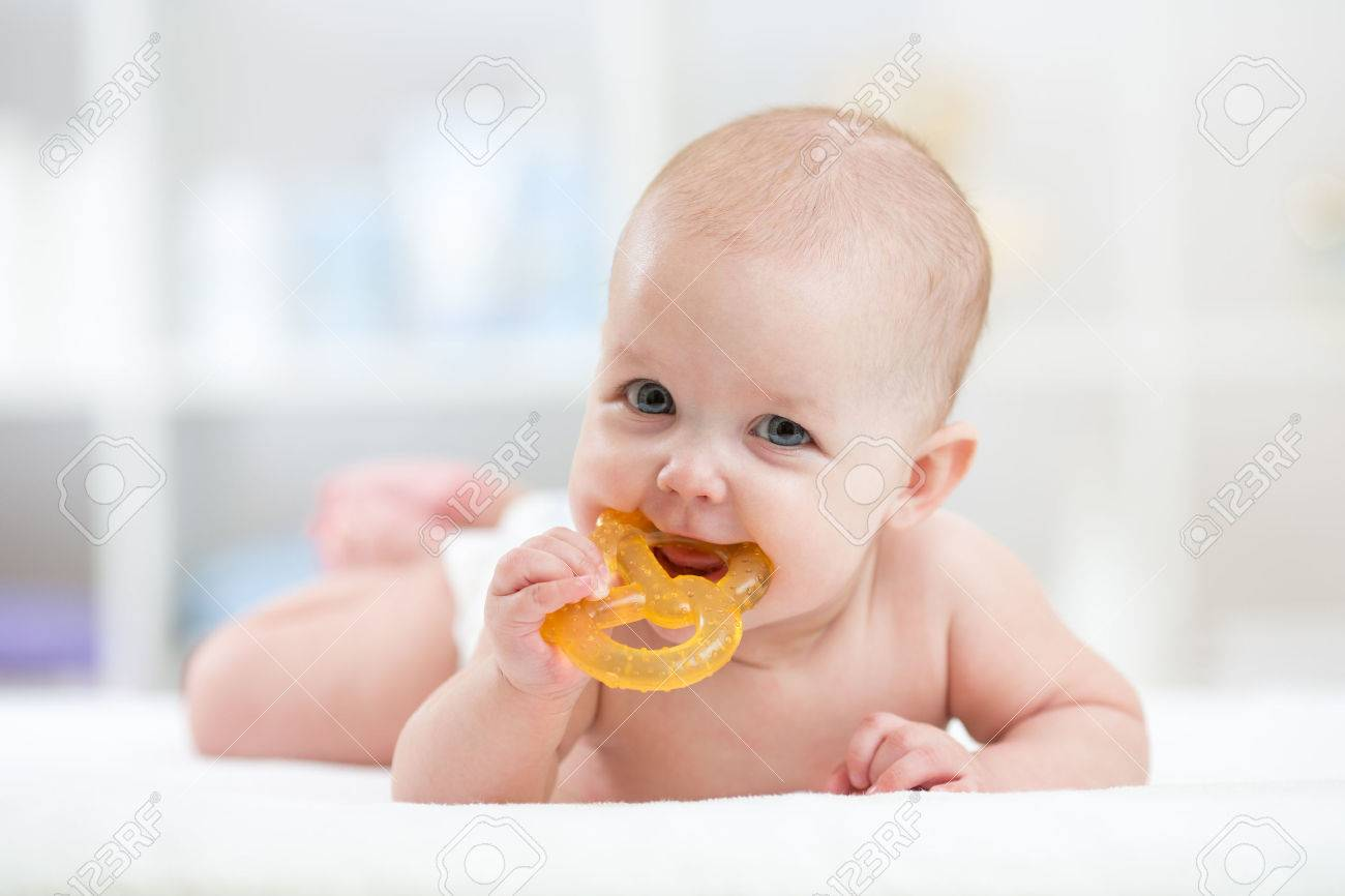 baby little child lying on bed weared diaper with teether Stock Photo - 54270483