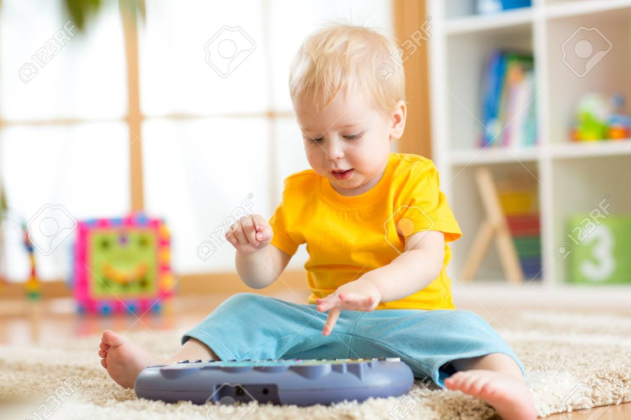 Happy kid boy playing piano toy in nursery room Stock Photo - 58617190