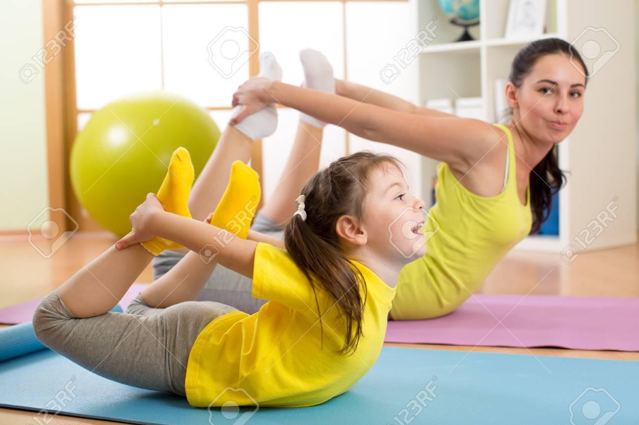 mere et enfant fille a faire des exercices de yoga sur le tapis a la maison