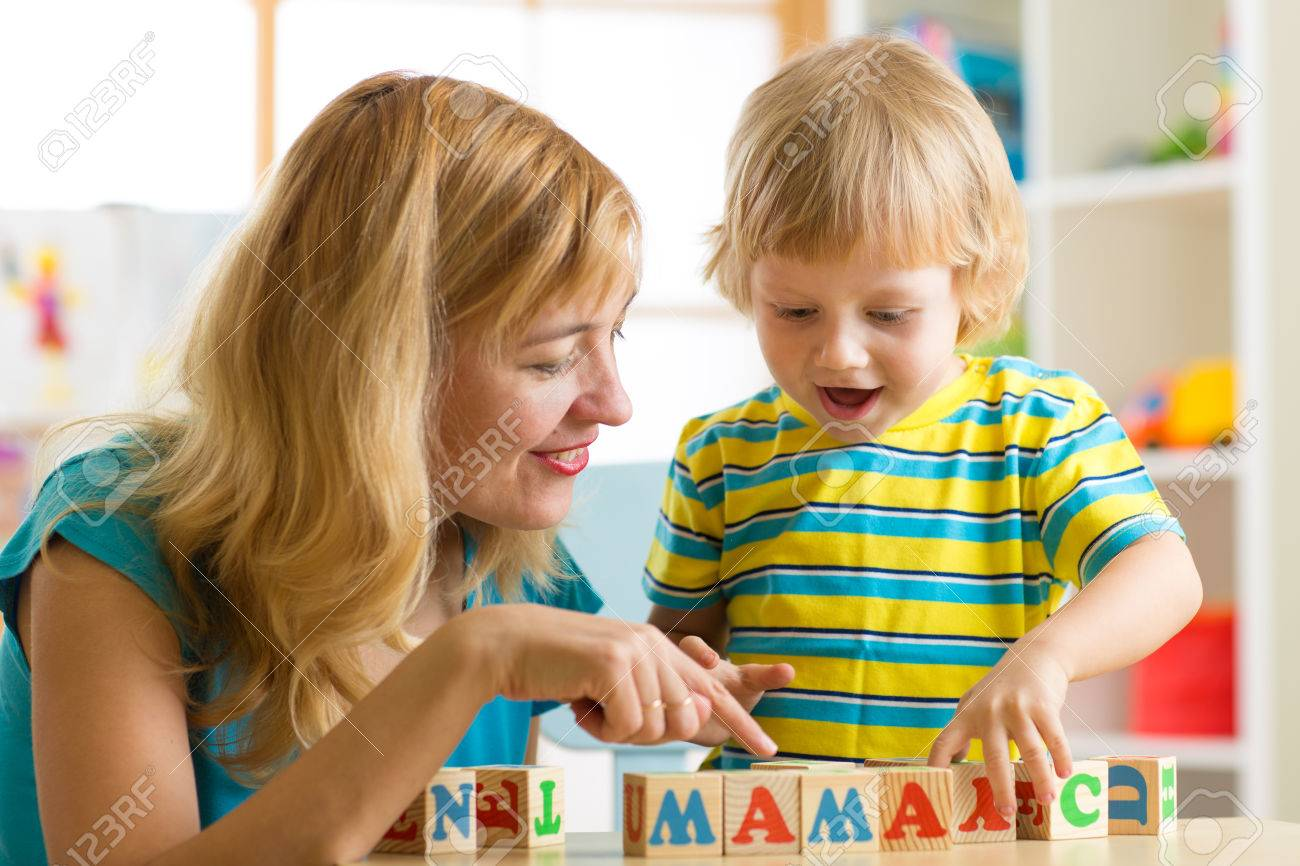 Mother teaches son child to read letters and words playing with