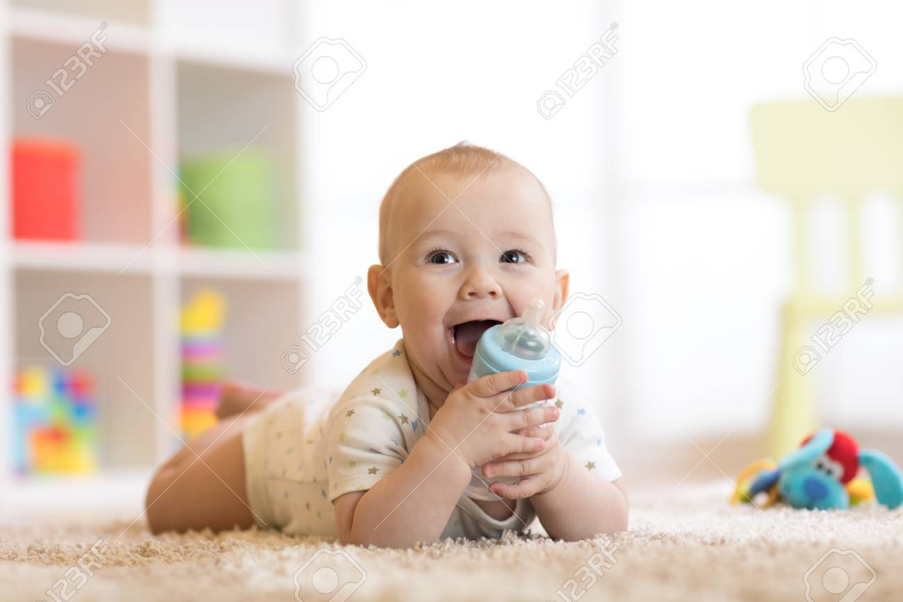 Pretty baby boy drinking water from bottle. Smiling child is 7 months old. - 91966392