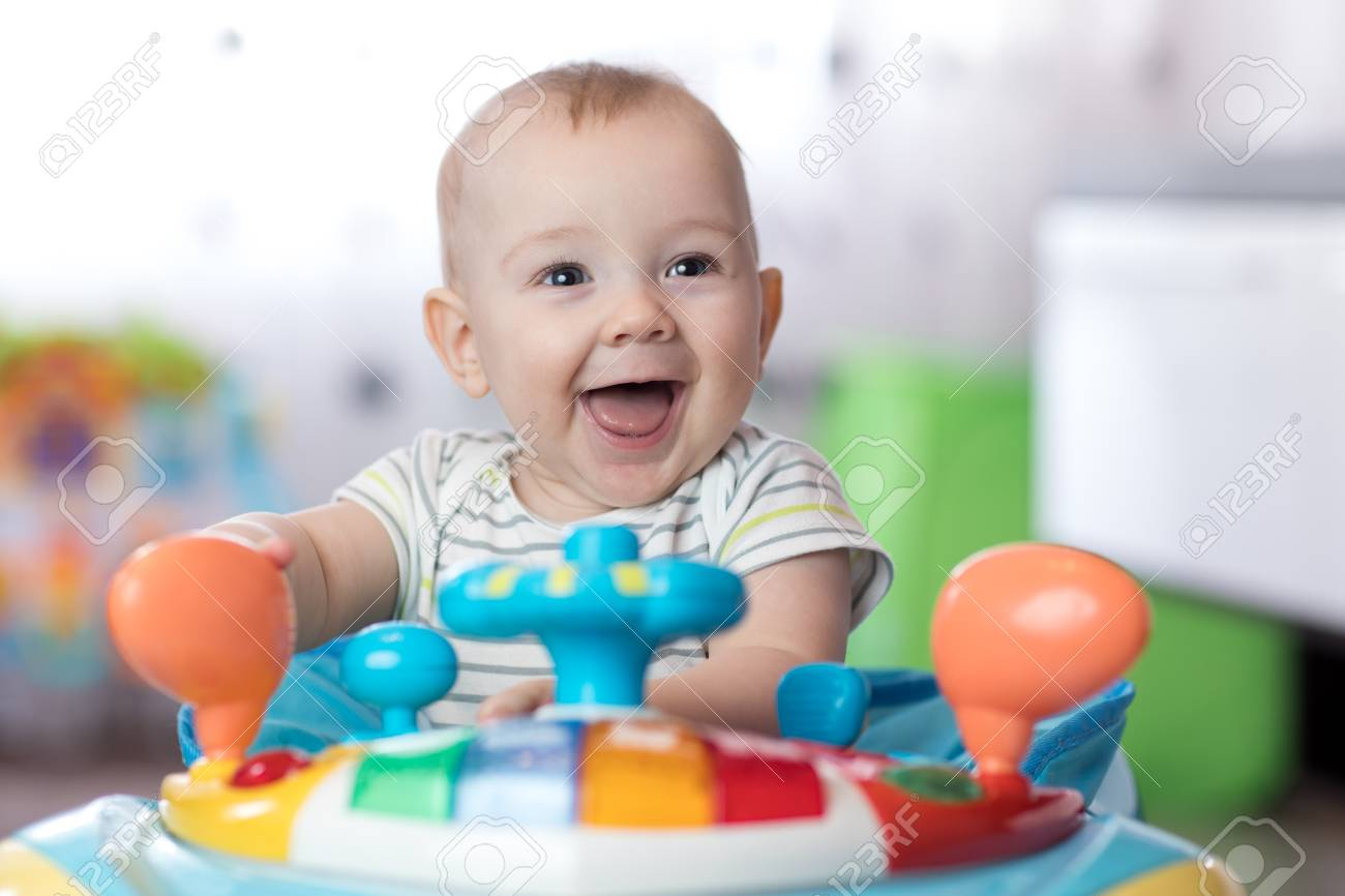 b86553bb9 Funny Baby Playing In Baby Jumper Stock Photo