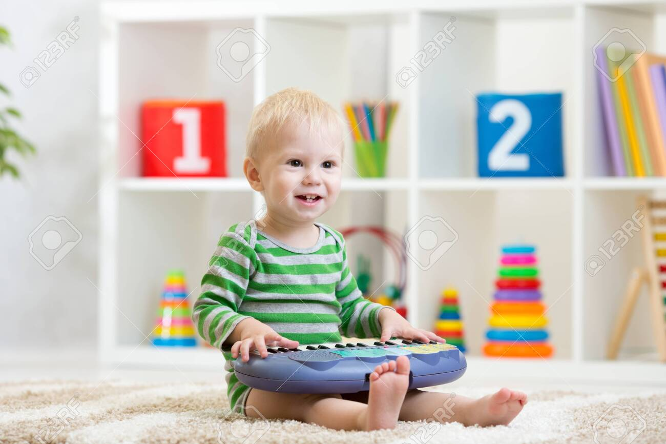 Kid boy playing toy piano in nursery - 121461876